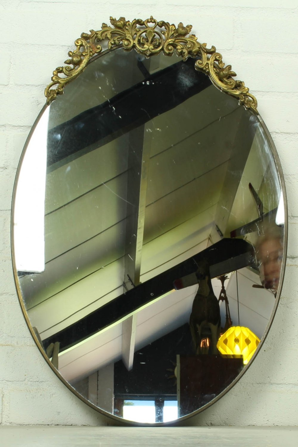 Antique oval wall mirror in brass frame with top ornament