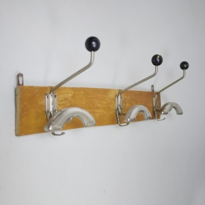 A three arm coat rack with wooden knobs