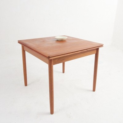 A quadratic, smaller teak dining table with extensions under tabletop