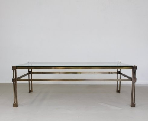 Glass coffee table in brass colored metal frame