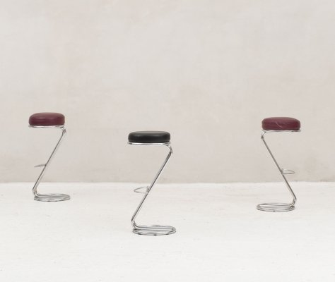 Set of three bar stools on a chrome base with foot rests