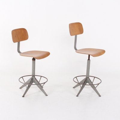 Pair of industrial stools with compass shaped legs