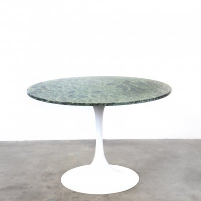 Round dining table with green marble top on a trumpet shaped foot