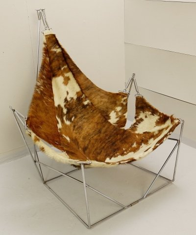 Mid Century Lounge Chair in Cow-hide hanging on suspended chrome spring frame