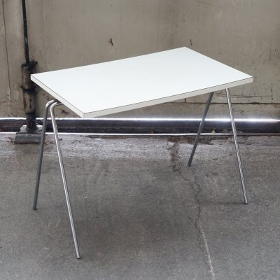 Low, white side table with inclined legs in chrome