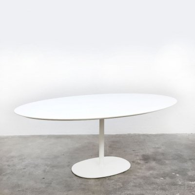 Oval table with white table top on a trumpet shaped base
