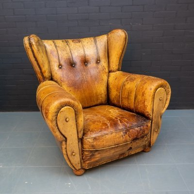 Large vintage wing chair made of sheep leather