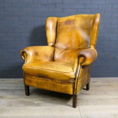Vintage sheepskin leather armchair with decorative nails