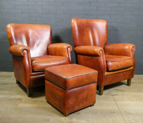 Set of 2 vintage sheep leather armchairs including 1 footstool