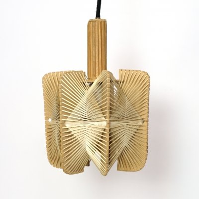 Pendant made of strings tied around a wooden structure